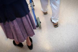 Elderly Woman Walking with Nurse in Nursing Home
