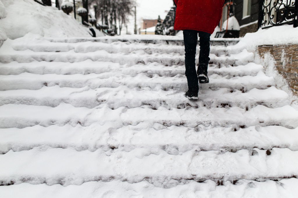Woman Climbs Stairs in the Snow